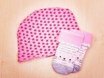 Babygoederen Babyblouse en pijama van broekschuiven op de wasknijper op de kabel op houten Stock Foto
