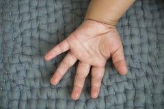 Babyhand auf einem grauen Sofa lizenzfreies stockfoto
