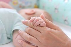 Babyhand in der Mutterhand stockfotos