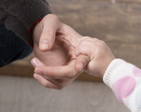 Babyhand, die Vaterfinger hält Stockfoto