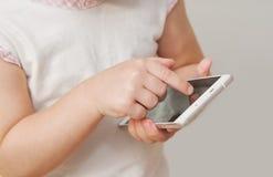 Babyhand, die weißes intelligentes Telefon auf weißem Hintergrund zeigt Stockbilder