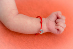 Babyhand mit rotem Armband Stockbild