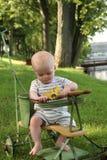 Babyjongen in antieke wandelwagen dichtbij water in binnenplaats Royalty-vrije Stock Foto's