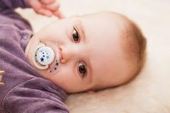 Babyjongen, bruine ogen, witte droevige achtergrond, fopspeen Stock Foto's
