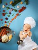 Babyjongen in chef-kokhoed met het koken van pan Stock Afbeelding