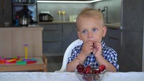 Babyjongen die kersen eten die in keuken zitten Kersen in plaat op lijst gimbal stock footage