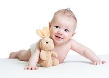 Babyjongen die met pluchestuk speelgoed liggen Stock Afbeeldingen