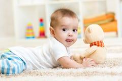 Babyjongen die met pluchestuk speelgoed liggen Stock Foto's