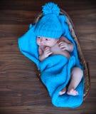 Babyjongen die op blauwe deken in de mand leggen Stock Foto's