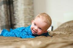 Babyjongen die op buik liggen Stock Foto's