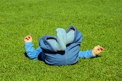 Babyjongen die op een gras in een park liggen Royalty-vrije Stock Foto's