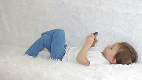 Babyjongen die op laag het spelen met een smartphone liggen stock videobeelden