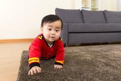 Babyjongen die op tapijt kruipen stock foto's