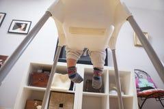 Babyjongen die op TV op zijn highchair letten Stock Foto