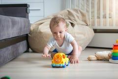 Babyjongen die op vloer kruipen en voor stuk speelgoed auto bereiken stock foto's