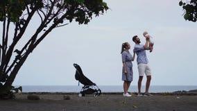 Babyjongen die over de schouder van zijn papa leunen neuzen met zijn mooie glimlachende moeder speels om te raken stock footage