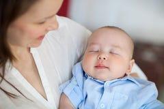Babyjongen die in slaap in de wapens van haar moeder vallen Royalty-vrije Stock Foto's