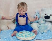 Babyjongen die terwijl het eten van zijn cake van de verjaardagspartij schreeuwen Royalty-vrije Stock Foto