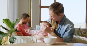 Babyjongen die terwijl moeder die hem voedsel 4k voeden schreeuwen stock video