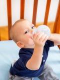 Babyjongen die in voederbak een fles houden Stock Fotografie