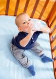 Babyjongen die in voederbak een fles houden Royalty-vrije Stock Afbeeldingen