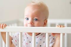 Babyjongen die zich in voederbak bevinden stock afbeelding