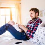 Babyjongen door zijn vaderzitting wordt gehouden op bed dat Stock Afbeelding