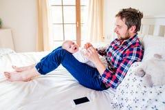 Babyjongen door zijn vaderzitting wordt gehouden op bed dat Stock Afbeeldingen