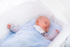 Babyjongen in een voederbak onder gebreide deken Royalty-vrije Stock Fotografie