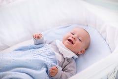 Babyjongen in een voederbak onder gebreide deken Stock Fotografie