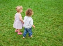 Babyjongen en babymeisje in het park Stock Afbeeldingen