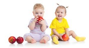 Babyjongen en meisje die gezond geïsoleerd voedsel eten Stock Afbeeldingen
