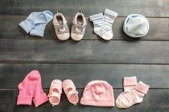 Babyjongen en meisjesschoenen en sokken op blauwe houten achtergrond royalty-vrije stock afbeeldingen