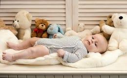 Babyjongen in gestreepte bodysuit Baby die op wit dekbed liggen royalty-vrije stock afbeelding