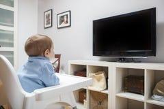 Babyjongen het letten op televisie in woonkamer Stock Afbeeldingen