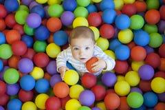 Babyjongen het spelen in de pool van speelplaatsballen Stock Foto's