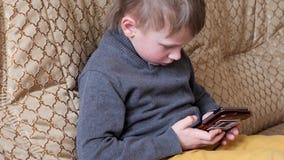 Babyjongen het spelen in de telefoonzitting op de laag stock video