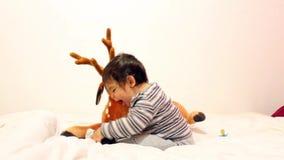 Babyjongen het spelen met beste stuk speelgoed en het verwijderen van zijn sokken met een schuwe glimlach stock videobeelden