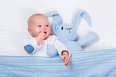 Babyjongen het spelen met blauw gebreid konijntjesstuk speelgoed Stock Foto's