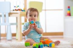 Babyjongen het spelen met kleurrijke plastic bakstenen op de vloer Peuter die pret hebben en van aannemersbakstenen uitbouwen stock afbeeldingen