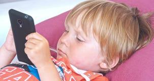 Babyjongen het spelen met mobiele telefoon stock footage