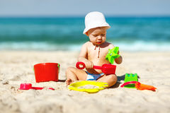 Babyjongen het spelen met speelgoed en zand op strand Stock Foto