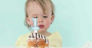 Babyjongen het vieren eerste verjaardags blazende kaars stock videobeelden