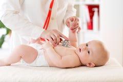 Babyjongen in luier tijdens medisch De arts onderzoekt jong geitje met stethoscoop Stock Afbeelding