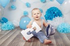 Babyjongen met blauwe ogen blootvoets in broek met bretels en hoed, die op houten vloer in studio zitten, die grote brief E, loo  Stock Fotografie