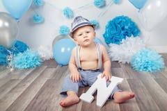 Babyjongen met blauwe ogen blootvoets in broek met bretels en hoed, die op houten vloer in studio zitten, die grote brief N, loo  Royalty-vrije Stock Foto