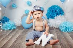 Babyjongen met blauwe ogen blootvoets in broek met bretels en hoed, die op houten vloer in studio zitten, die grote brief N, loo  Stock Foto