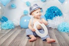 Babyjongen met blauwe ogen blootvoets in broek met bretels en hoed, die op houten vloer in studio zitten, die grote brief O, loo  Royalty-vrije Stock Fotografie