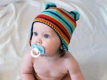 Babyjongen met fopspeen in multicolored gebreid GLB Stock Foto