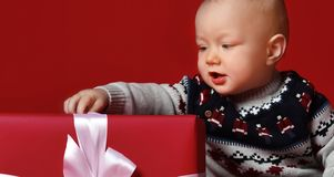 Babyjongen met grote blauwe ogen die warme sweaterzitting voor zijn heden in verpakte doos met lint over rode achtergrond dragen stock fotografie